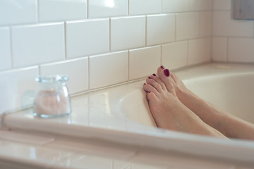 Women's feet with dark purple nail polish in a luxurious bathtub. surrounded by white subway tile.  a small glass container of pink bath salts rests at the edge.