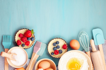 Baking utensils and cooking ingredients for tarts, cookies, dough and pastry. Flat lay with eggs, flour, sugar, berries.Top view, mockup for recipe, culinary classes, cooking blog.