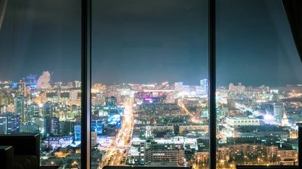 Fotobehang - Night city skyline, view from dark room with panoramic window silhouette,  illuminated cityscape in background. Timelapse, 4K UHD. Zoom in.