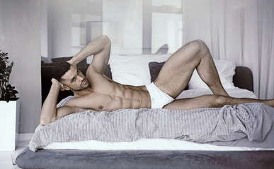 Aluminium Prints Artist KB Muscular, fit man laying on a bed in a luxurious apartment