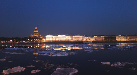 Incredibly beautiful view of the Neva river and St. Isaac's Cathedral at night. Illumination of streets and buildings in the center of St. Petersburg during the spring ice drift