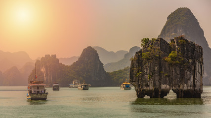 Beautiful sunset Tourist junks floating among limestone rocks at Ha Long Bay, South China Sea, Vietnam, Southeast Asia.