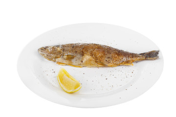 Fish trout whole with a head baked fried over an open fire with a slice of lemon and ground pepper. Appetizing juicy natural, on white isolated background View from above For the menu restaurant bar