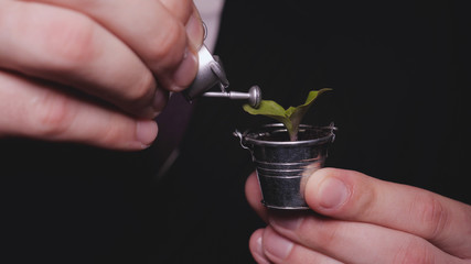 A businessman in a suit holds a sprout in a mini bucket and a watering can, a black background, a career growth, a new life.