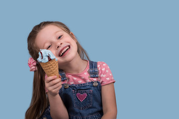 The little girl  cheerfully eats ice cream in wafer gunny on blue background in studio with copy space.