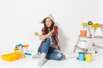 Cute woman in newspaper hat sitting on floor with brush, instruments for renovation apartment room isolated on white background. Wallpaper, accessories for gluing, painting tools. Repair home concept.