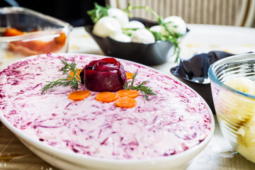 preparing russian traditional salad 'herring under fur coat'