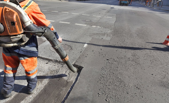Partial repair of the asphalt road. The worker cleans the bad part of the road with an industrial vacuum cleaner