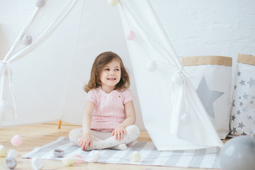 Cute little 3 year old girl sitting and smiling in pink dress in tent lodge . Portrait of a funny toddler in the nursery interior. Soft pastel color, white, grey and pink. Happy childhood moments
