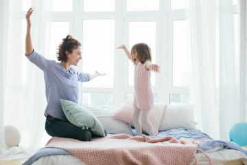 Young mother and her little daughter jumping on bed. Funny pillow fight. Soft pastel colors, pink and blue. Selective focus. Play together and enjoy the moment! Family time on weekend.