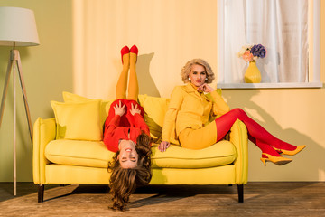 retro styled beautiful girls in red and yellow dresses on sofa at home