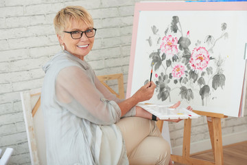 Cheerful woman painting flowers