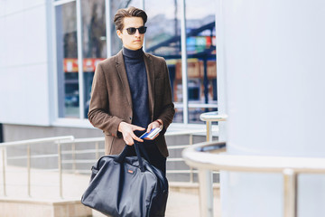 stylish attractive guy in jacket with passport and tickets