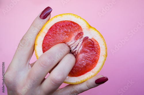 Two fingers on grapefruit on pink background. Sex concept