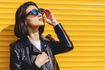 Beautiful girl sunglasses on bright yellow background