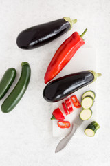 Aubergines, Sweet Pointed Peppers and Courgettes on Chopping Board