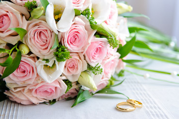 Gold wedding rings and a bouquet of the bride with pink roses.
