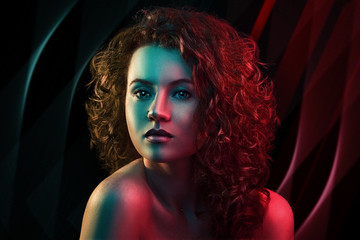 Portrait of cute red head girl with curly hair in colorful bright lights posing in studio. Background as in a nightclub