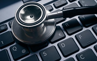 Computer virus concept image. Stethoscope lying on keyboard.