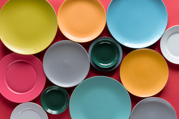 Shiny colorful kitchen ceramic plates on red background