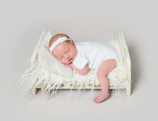 Lovely newborn baby sleeping on crib with leg on the floor