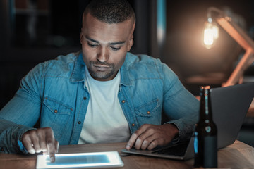 Software engineer. Afro American concentrated IT guy using tablet while staring down and sitting at table