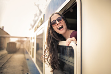 Excited girl traveling by train, looking out from the window