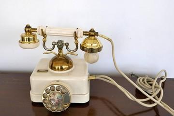 Sehr altes weiß-goldenes Telefon mit drehbarer, verzierter Wählscheibe, Hörer und Schnur