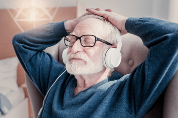 Absolute relaxation. Nice relaxed aged man wearing headphones and closing his eyed while listening to music