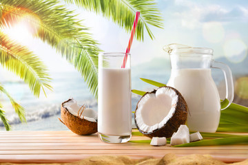 Coconut milk in containers and fruit on the beach