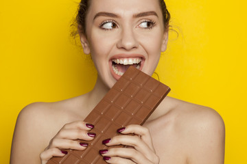 young happy woman enjoying eating chocolate on a yellow background