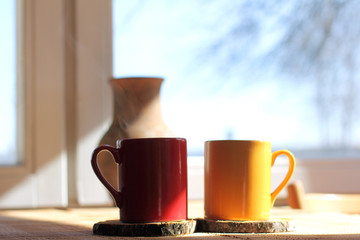 coffee pause overlooking the landscape/ red and orange mug with a hot drink on the table in a rustic house