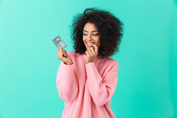 Portrait of charming american woman 20s with afro hairstyle holding plastic credit card with pleasure, isolated over blue background