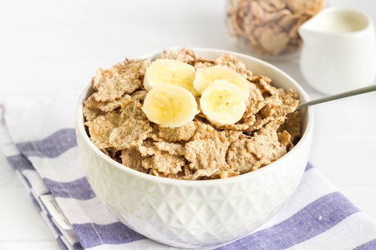 Whole wheat cornflakes with banana slices in white bowl