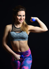 Fitness girl with dumbbells in hands posing on camera isolated on a black background. Biceps. Healthy life.