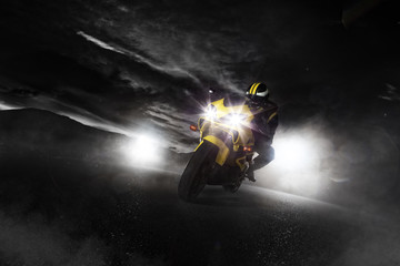 Supersport motorcycle driver at night with smoke around.