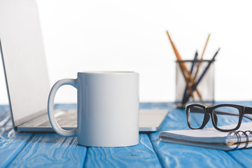 closeup shot of cup, eyeglasses on textbook, laptop and organizer with pens and pencils