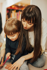Mother and daughter is drawing pictures at home