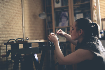 master woman near work bench works with tools