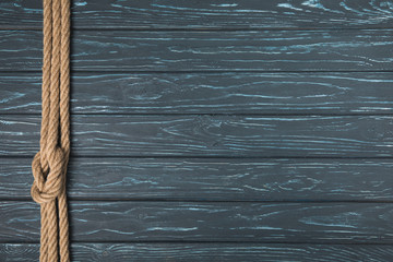 top view of background with brown nautical rope with knot on wooden planks