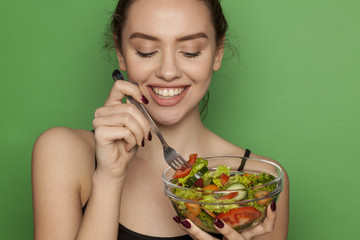 Young beautiful woman eating salad on green background