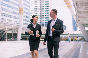 Asian business woman holding document file and plastic mug on hand talk about business future with  Caucasian businessman. they are walk together in the city.
