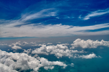 Beautiful blue sky and white clouds background. Sky atmosphere panorama. Heavenly bright daylights. Outdoor planet. Photo from the aircraft window.