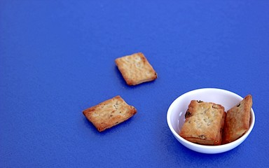 Crispy salted wheat crackers in a white plate on a blue background