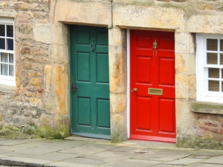 Red and green front doors on adjoining terraced homes in the UK, Lancaster, Lancashire