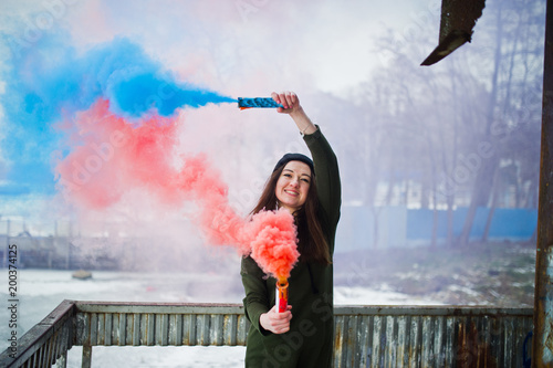 Young girl with blue and red colored smoke bomb in hands