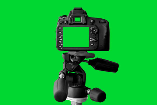 The Dslr camera with green screen on the tripod isolated on green background. The chromakey. Green screen.
