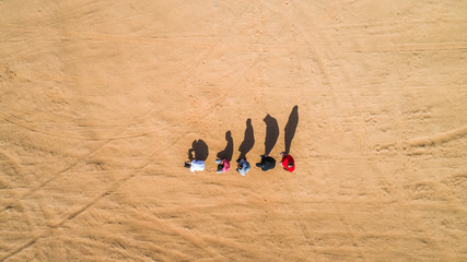 Aerial view of friends imitating human evolution with shadows in Sharjah desert.
