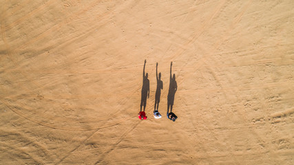 Aerial view of friends waving with their shadows in the Sharjah desert.