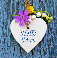 Hello May greeting card with decorative white heart and spring flowers on old blue wooden background.Springtime concept.Selective focus.